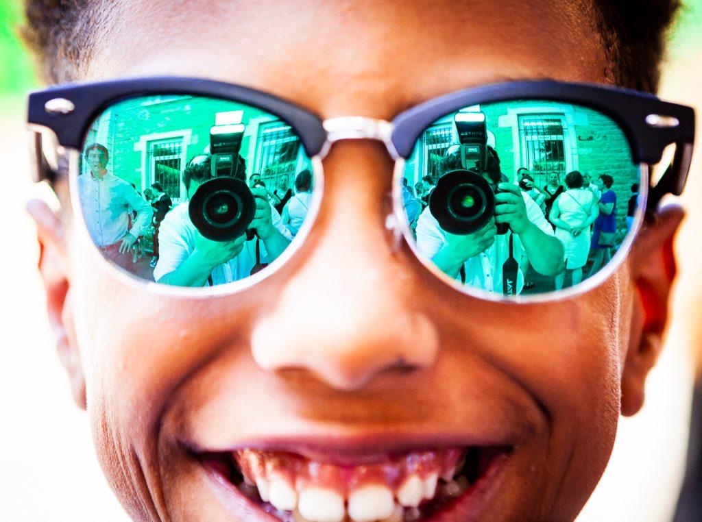 autoportrait de philippe cotin photographe de mariage dans le reflet des lunettes de soleil d'un enfant souriant
